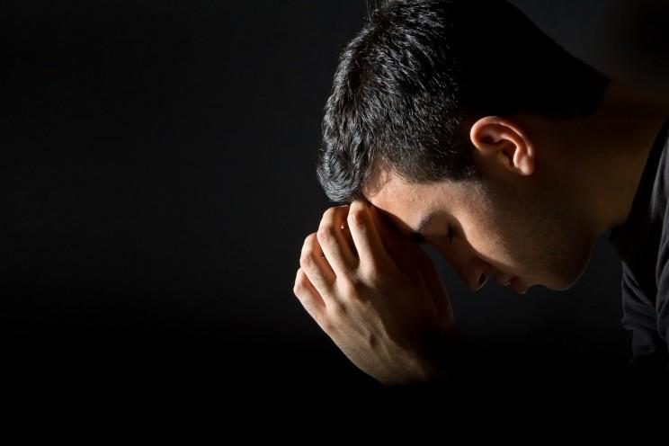 Young man praying in the dark