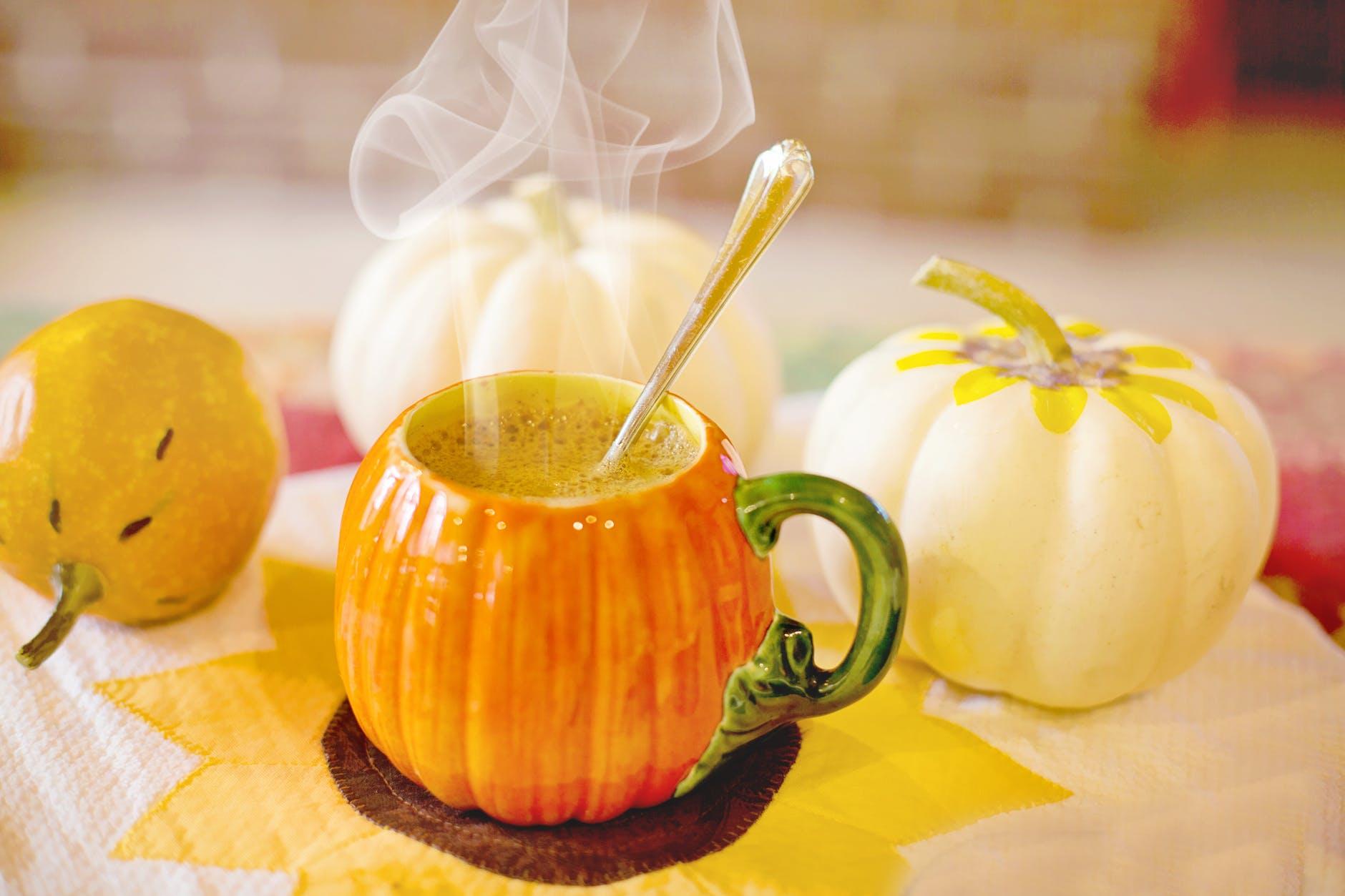 orange juice in green ceramic mug