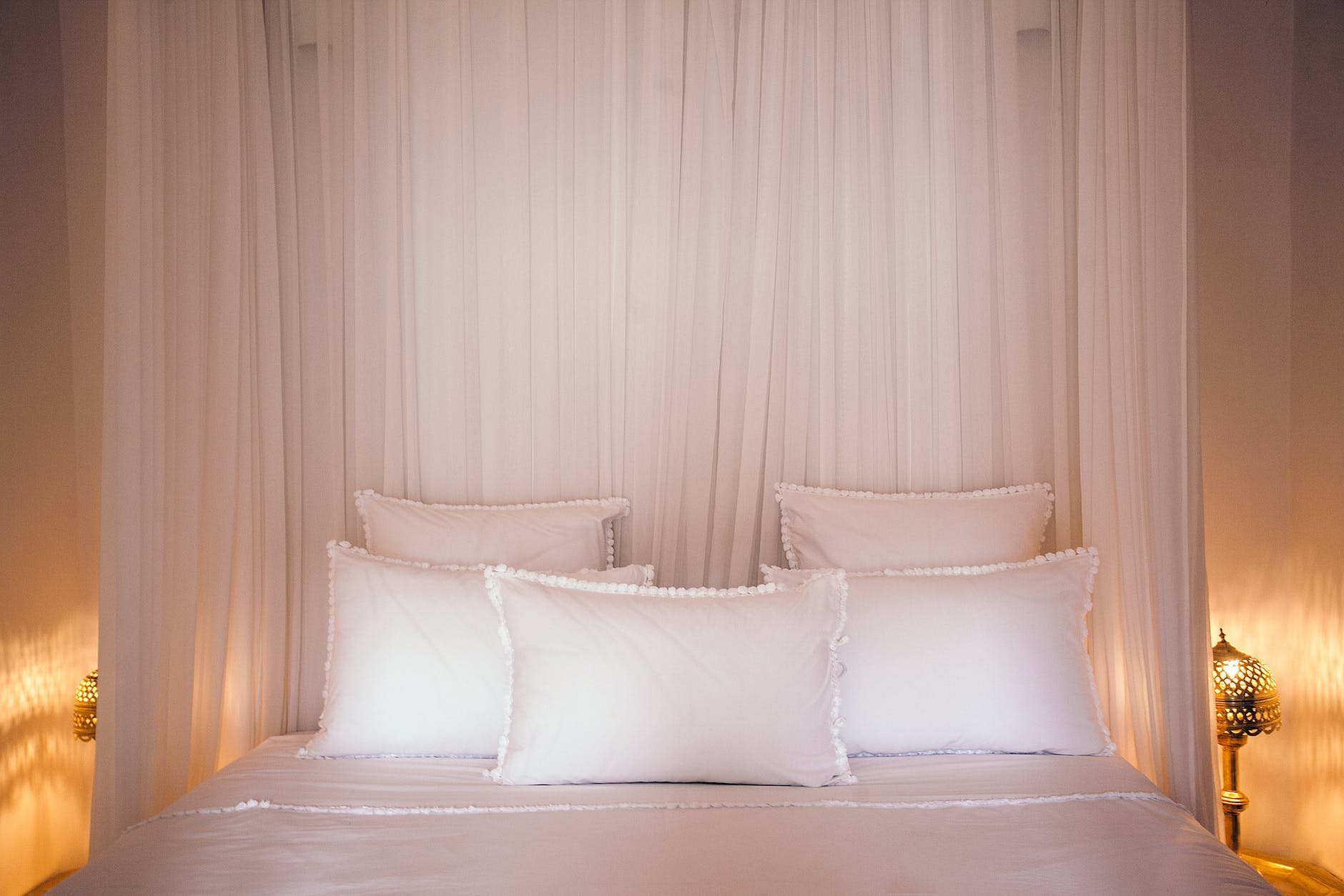 cozy bed with pillows and white canopy