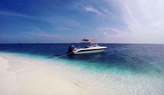 speedboat in clear water white sand beach