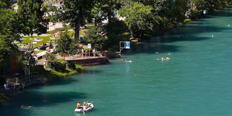 people swimming, tanning and boating in the Aare River next to Marzili