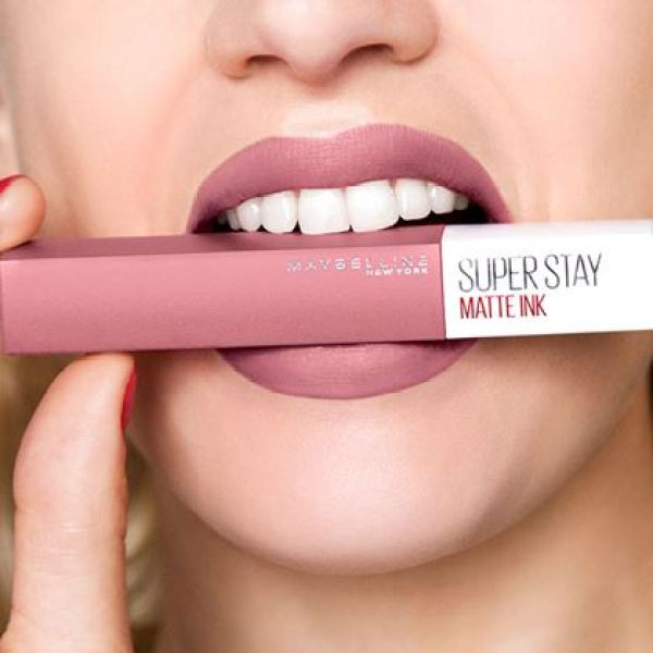 woman biting on lipstick maybelline super stay
