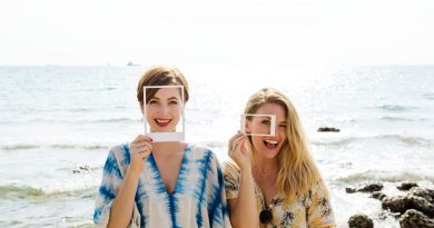 two women smiling with makeup and picture frames by the beach
