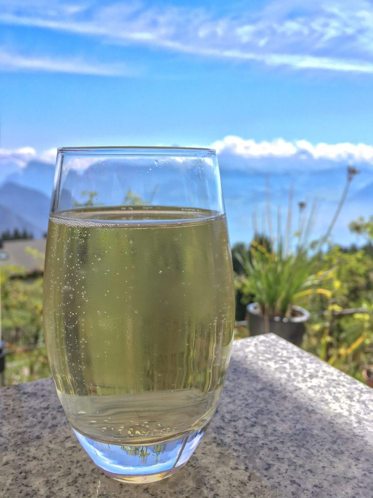 yellow rigi cola made from herbs in a clear glass with the swiss alps in the background