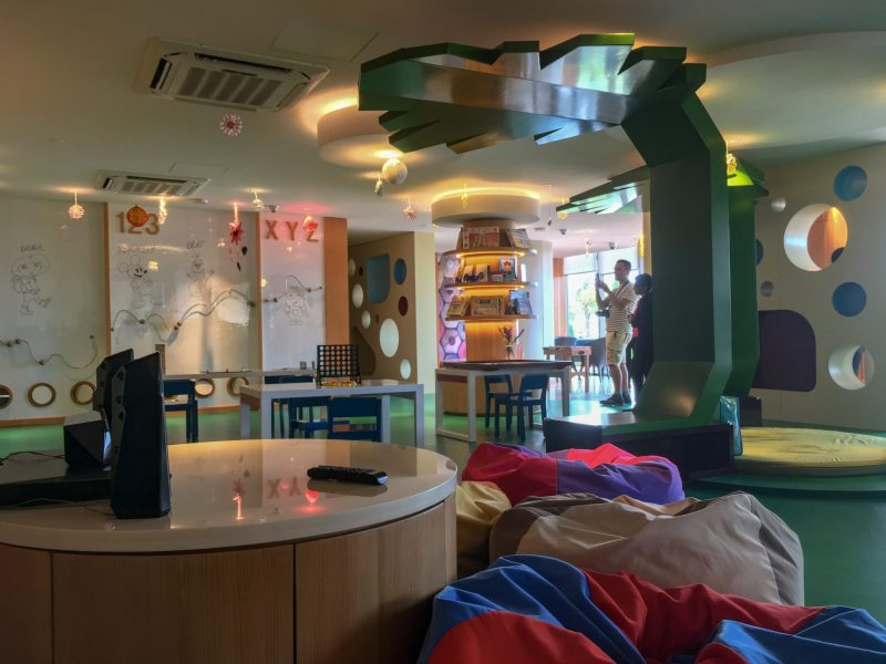 inside the kids club room with bean bags, art wall and play areas