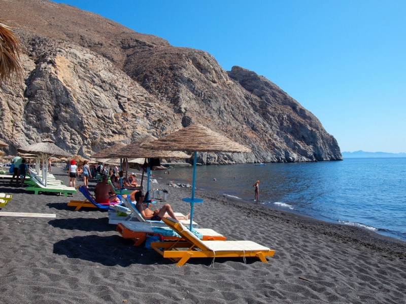 people suntanning under parasols on the black beach of perissa santorini