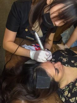 eyebrow embroidery technician performing mist semi permanent makeup using embroidery pen on woman