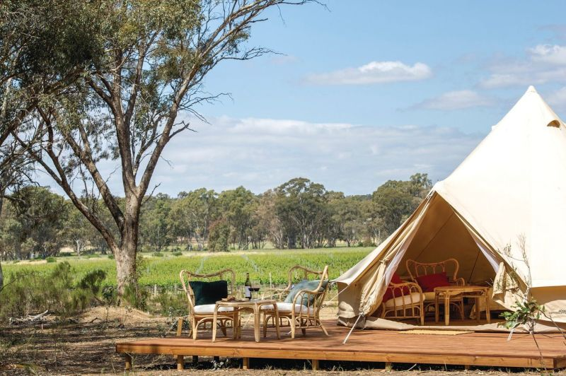 large white camping tent for glamping with outdoor patio and wine on table within a vineyard