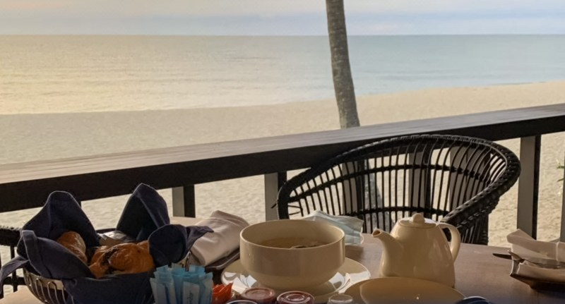 basket of pastries, coffee pot, breakfast jams on a table overlooking teluk cempedak beach at kampung restaurant hyatt