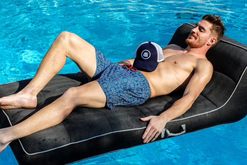 man lazing on flatie bed with a cap and blue luxury swim shorts