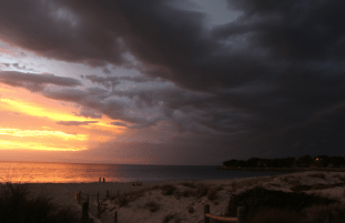 Half storm, half sunset, dark clouds rolling in over the ocean and yellow sunset to the left