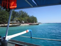 View from the boat looking towards Gili T, beautiful blue water, clear skies and a few small boats tied to the shore