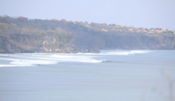 View of the surf in Padang Padang from atop a dirt track to the cliff edge