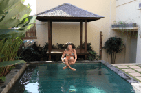 action shot, tegan jumping from the bali hut into the pool, cross legged