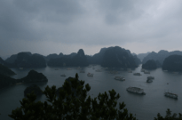 View over Ha Long Bay, cloudy grey skkies, 10 boats anchored in the bay, night ascending
