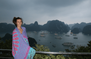 Tegan sitting on top of the lookout over Ha Long Bay, lots of boats anchored in the bay, tegan wrapped up in a purple pink and blue sarong
