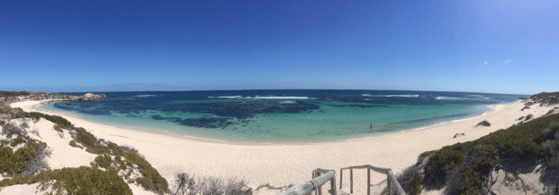 Panoramic shot of the beach, turquoise ocean so clear you can see the rocks, wooden footpath leading to the beach