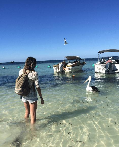Tegan walking into the ocean near a pelican