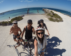 Group shot on our bicycles with our helmets on, ocean in the background, clear blue skies