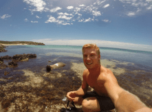 Dan taking a selfie with the sea lion in the shallows, blue skies, blue seas with a bit of seaweed