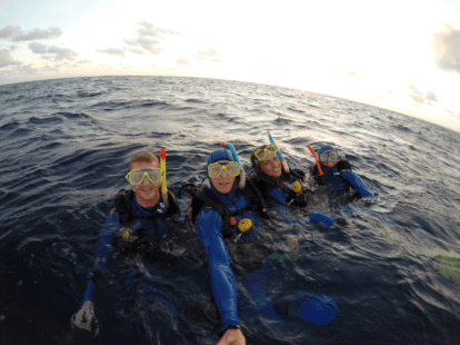 Group selfie above the water as the sun rises