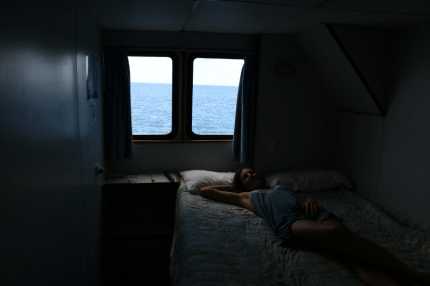 Tegan laying on the queen bed on the boat, double window with ocean views as far as the eye can see