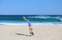 Tegan in handstand falling backwards, wave breaking behind her