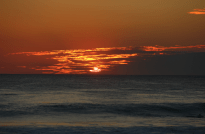 Sun sinking over the horizon, red and yellows in the sky, clouds to the right, and a calm ocean