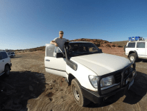 Dan standing up on the ledge with the door open to the landcruiser, blue clear skies above
