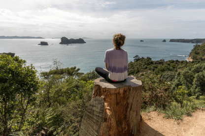 Tegan sitting on a tree stump overlooking the ocean, green shubbery below, a few small islands in the distance