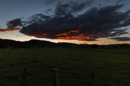Sunset over a farm with mountains in the background