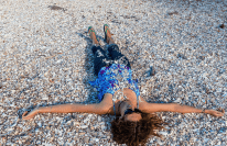 Tegan laying down arms outstretched covered in shells,