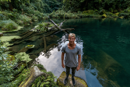 Dan standing in front of the bay at the waterfalls, water so clear you can see the logs and rocks below. Green ferns around the pool
