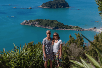 Couple shot on top of the mount, turquoise ocean behind us, Leisure island also in the background, green trees along the edge of the photos and clear blue skies