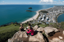 Girls sitting on the rocks on the top of Mount Maunganui, buildings below, white strip of sand, islands below and turquoise ocean