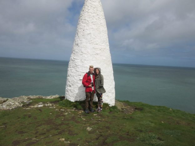 Tegan and Dan standing infront of a white rock double the height of them.