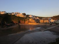 Looking back toward Little Haven from the lookout. Buildings glowing orange in the sunset colours