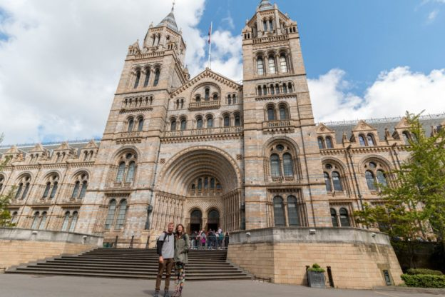 Tegan and Dan standing outside the museum, grand building wit 2 turrets on either side of the entrance