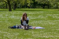 Tegan sitting on a sarong in Hyde Park eating some fresh strawberries for lunch, the green grass is covered with tiny white daisies