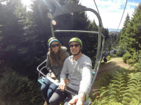 Tegan and Dan riding the chair lift back to the top, big pine trees behind the chair lift, ferns below