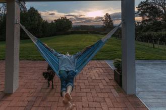 Tegan laying in a hammock, looking behind at the setting sun