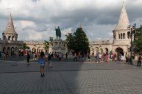 Tegan walking through a square towards are big statue