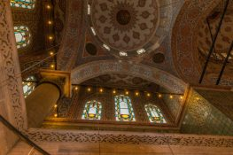 A circular area of rootop tiles, white and brown and reead and blue and 3 stained glass windows lit up