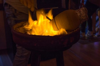 A clay pot with our dinner inside being cooked over a bright orange flame