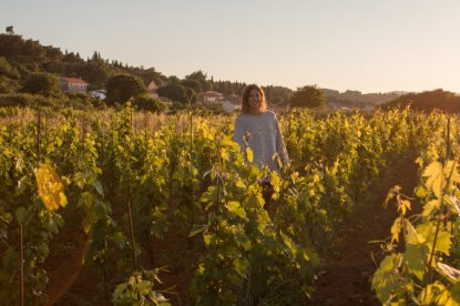 Tegan standing in the middle of a vineyard with the golden afternoon sun streaming down