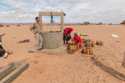 Watching a nomadic family 2 women and a girl filling water bottles from the well