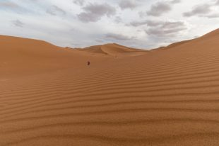 Lines in the desert sand, sand dunes in the distance, Tegan walking off towards them