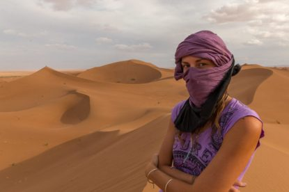 Tegan with her scarf over her head and mouth, dunes in the distance
