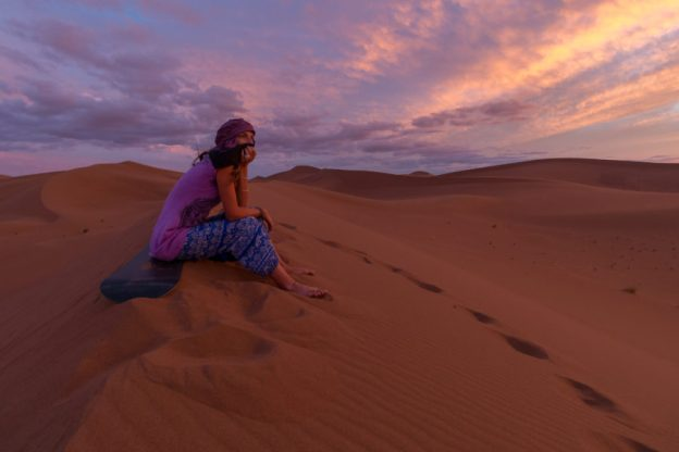 Tegs sitting on the dunes, pink and purples behind her