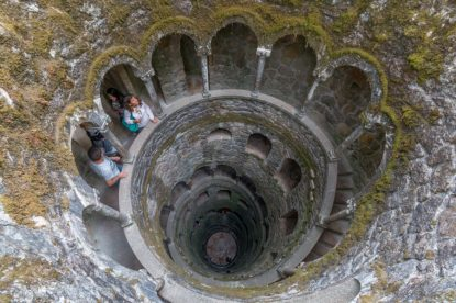 Inverted tower looking down from above, green moss covering the walls